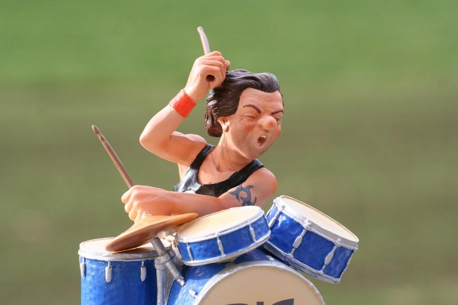 grafika przedstawia perkusistę grającego na niebieskiej perkusji