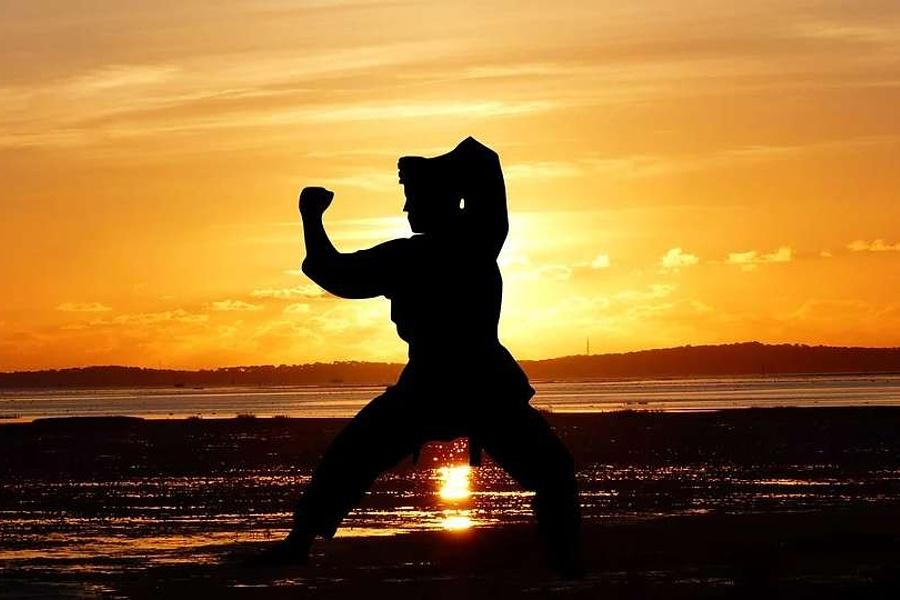 postać karateki, ćwiczącego o zachodzie słóńca