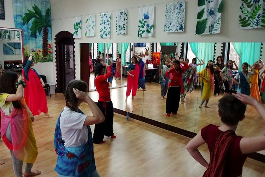 Grupa kobiet w różnym wieku, z kolorowymi szarfami przewieszonymi przez ramię stoi w tanecznej pozie przodem do lustra.