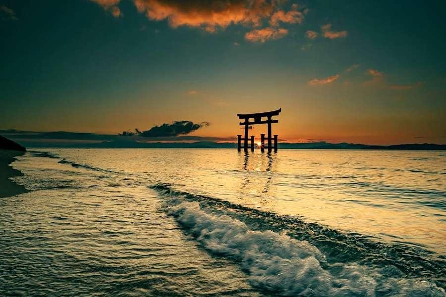 brama tori w morzu o zachodzie słońca