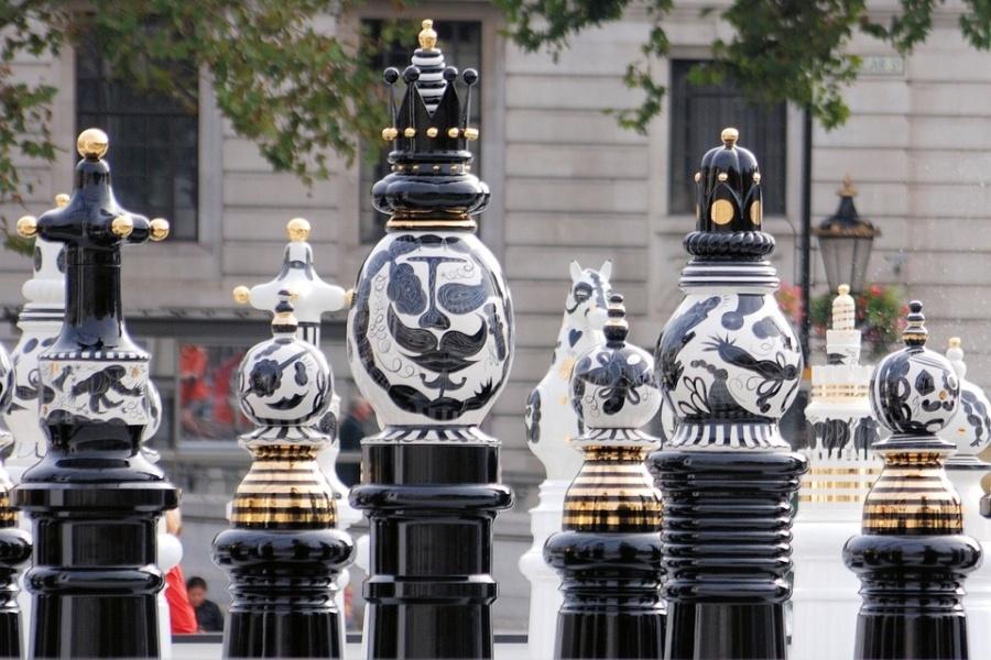 Figury szachowe na tle budynku.