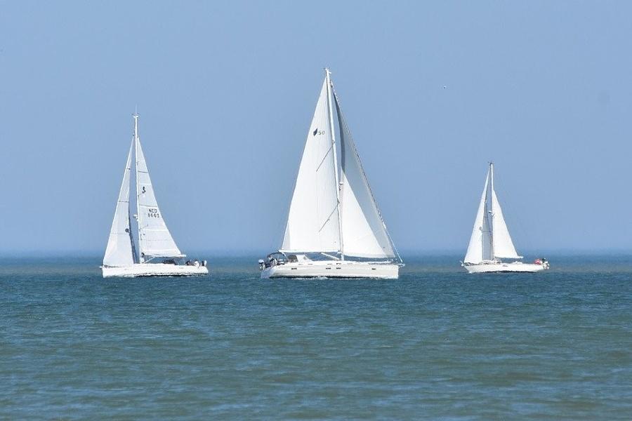 trzy jachty żaglowe płynące po morzy na tle zamglonego horyzontu