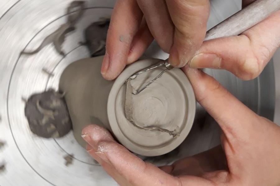 Dłonie trzymają ceramiczne narzędzie wybierające glinę z walca.