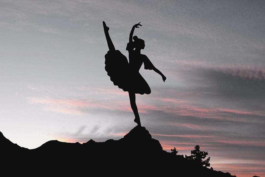Zdjęcie przedstawia tancerkę stojąca na skale z nogą i ręką uniesiona do góry