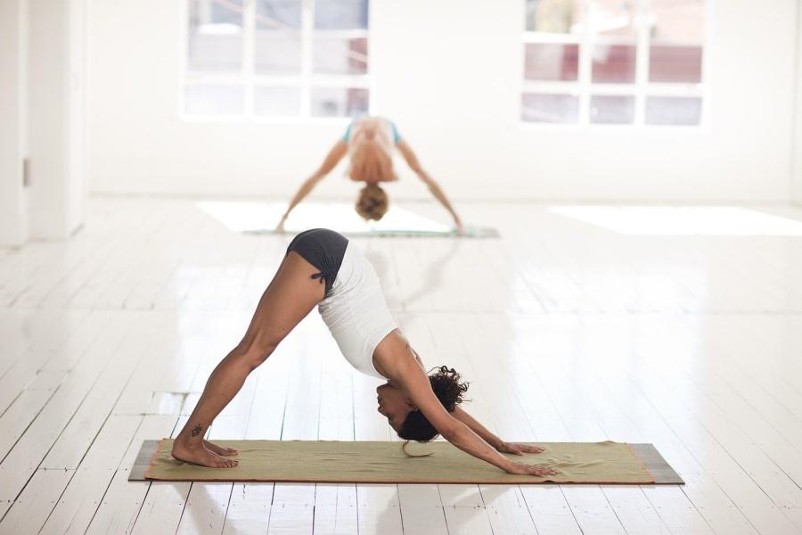 na zdjęciu kobieta ćwicząca jogę na maciew tle druga kobieta