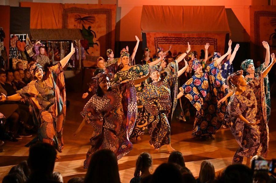 Grupa kobiet w kolorowych sukniach z motywami afrykańskimi, z turbanami na głowach, w tanecznej pozie z rękami do boku.