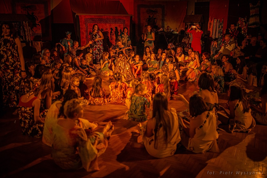 Duża grupa ludzi w różnym wieku, ubranych w kolorowe kostiumy siedzi na podłodze wokół sztucznego ogniska. Część stoi w tanecznej pozie.