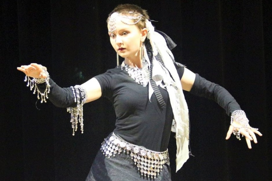 Kobieta w czarnej sukience ze srebrnym pasem i srebrnymi ozdobami na włosach i rękach stoi w tanecznej pozie na scenie.