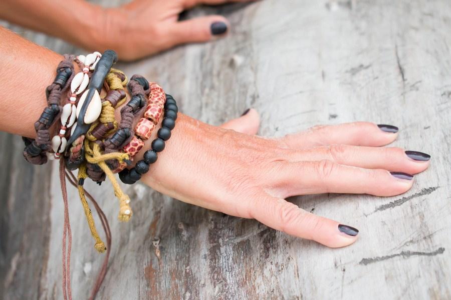 Dłonie z bransoletkami afrykańskimi ze sznurków, koralików, muszelek oparte o pień drzewa.