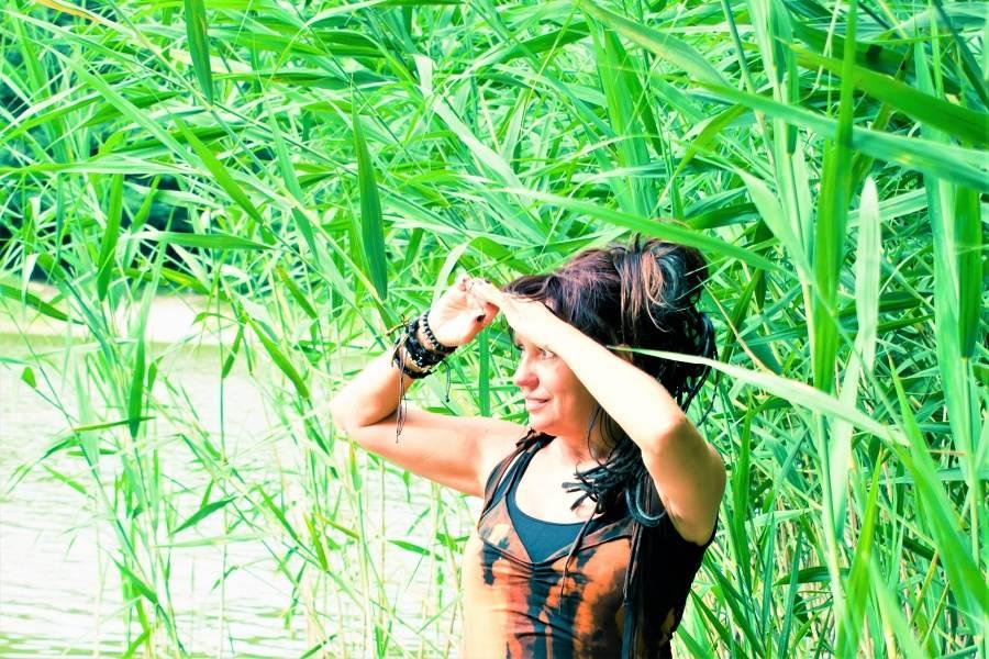 Kobieta ubrana w czarno-brązowy kostium z dłońmi uniesionymi na wysokość wzroku patrzy przed siebie. W tle zielone trawy.