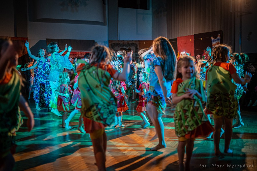 Grupa uśmiechniętych osób, ubranych w kolorowe, afrykańskie kostiumy tańczy na scenie.