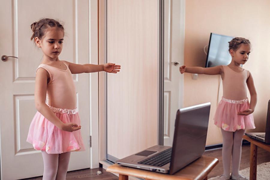 dziecko w pozycji baletowej przed komputerem