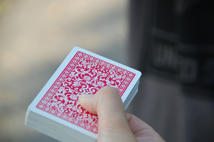 Talia kart o czerwonym rewersie trzymaja jedną ręką na szarym, miejskim tle