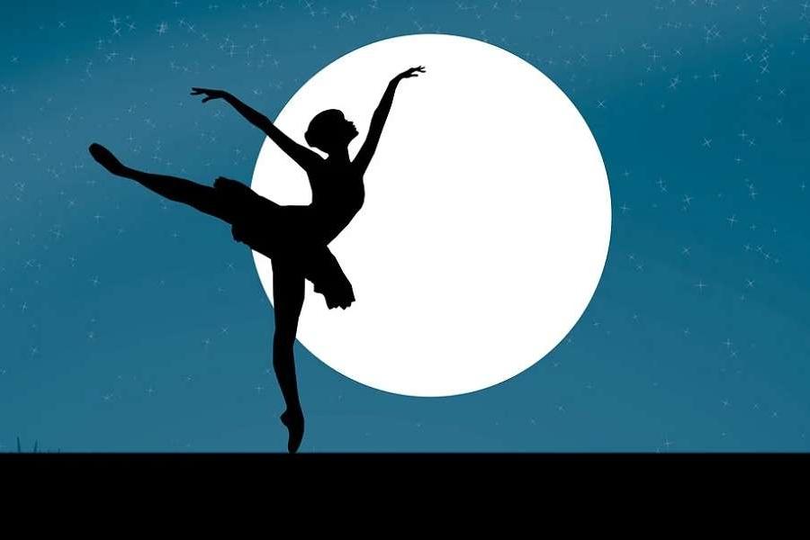 Zdjęcie przedstawia sylwetkę tancerki w pozie arabesque przy blasku pełni księżyca.