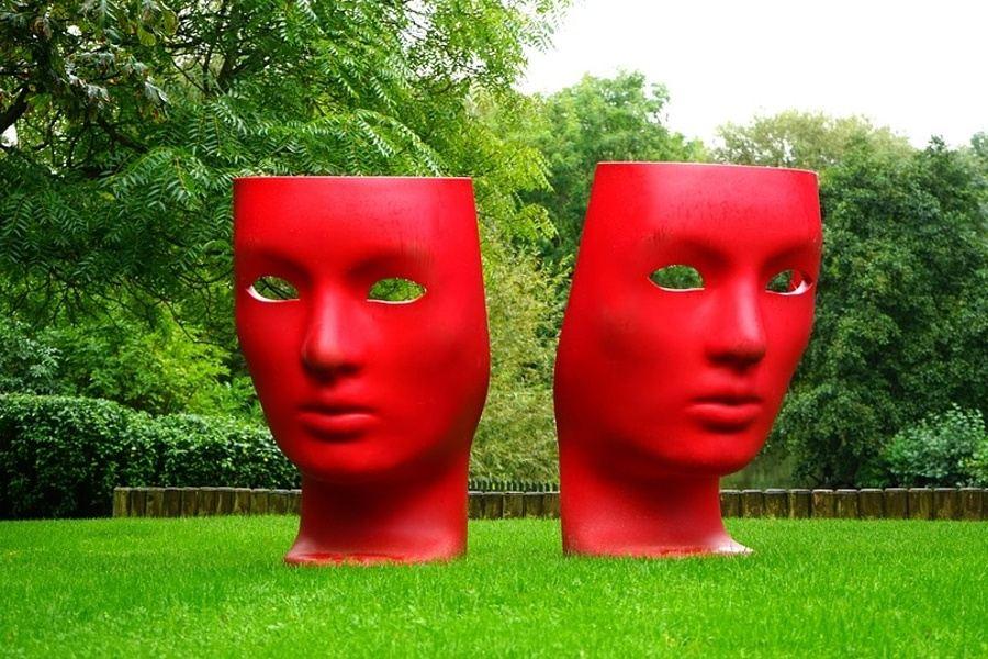 dwie duże czerwone maski stojące na trawniku