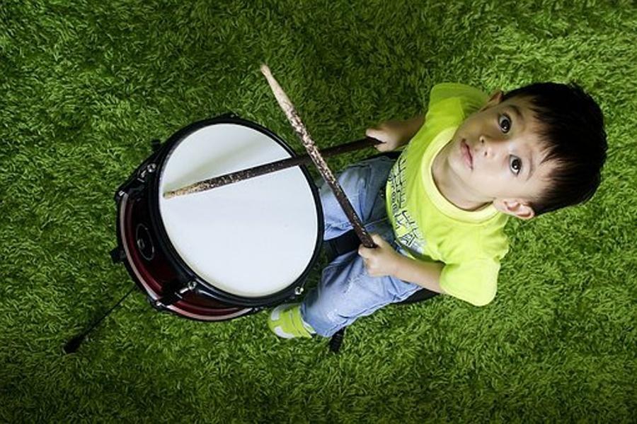 Zdjęcie przedstawia chłopca grającego na werblu