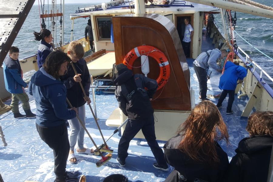 Na zdjęciu widzimy młodych żeglarzy szorujących szczotkami ryżowymi pokład żaglowca, który jest zlany wodą oraz detergentem do mycia.