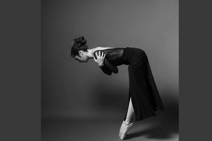 Zdjęcie przedstawia tancerkę stojącą na pointach. Sylwetka pochylona w przód, ręce splecione obejmujące ramiona.
