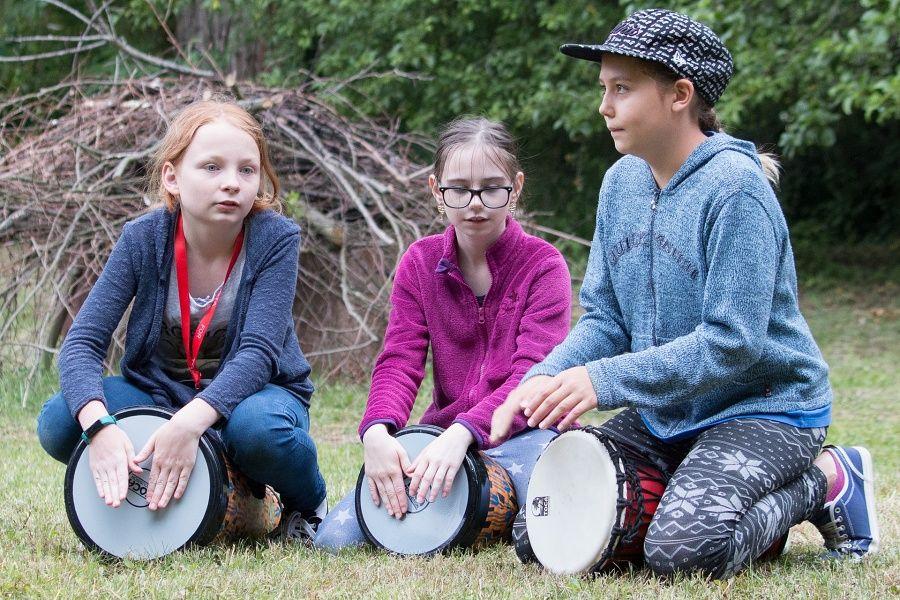 przedstawia trzy dziewczynki grające na djembe