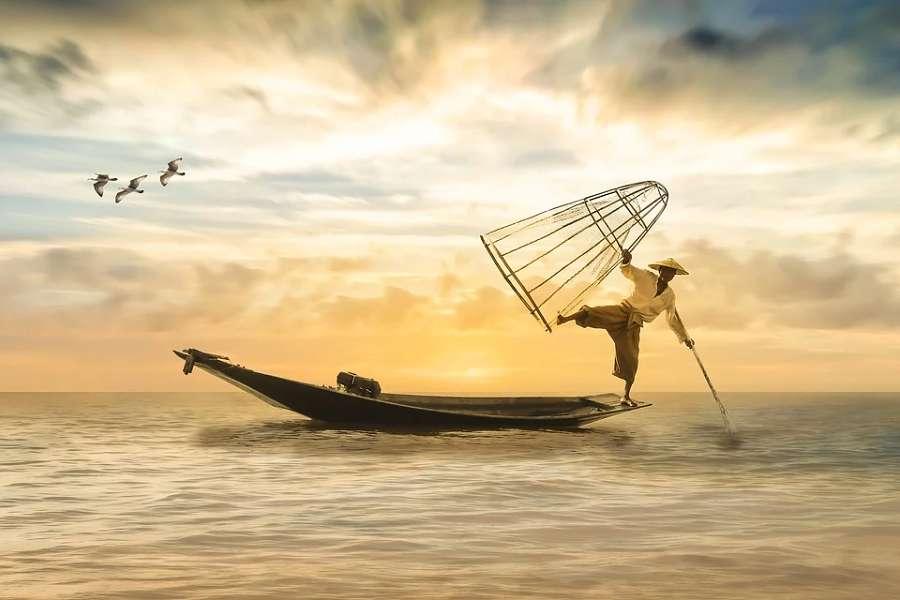 zdjęcie przedstawia japońskiego rybaka łowiącego na morzu.