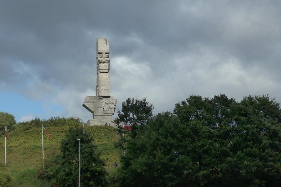 Gdańsk Westerplatte, wzgórze, na nim pomnik, drzewa i maszty z flagą.