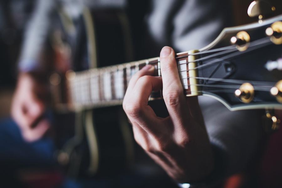 dłoń męska na strunach gitary