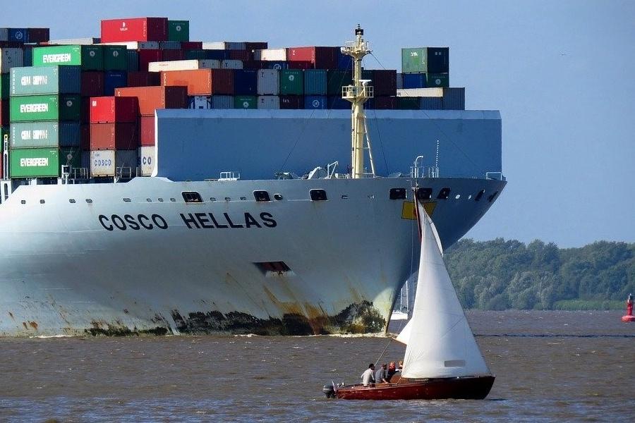Mały jacht żaglowy płynący blisko statku z kontenerami