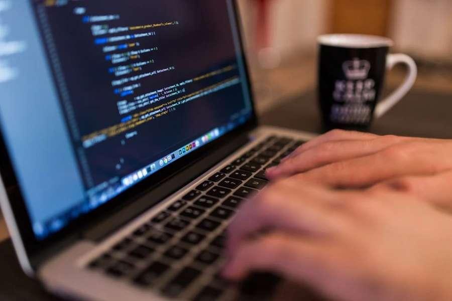laptop, na klawiaturze dłonie mężczyzny wpisują kod