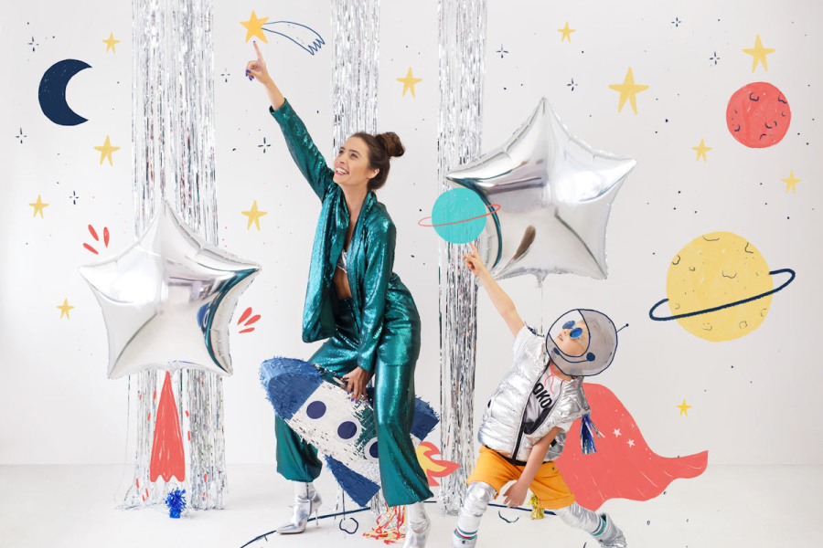 kobieta w błyszczącym zielono-turkusowym stroju i dziewczynka w srebrzystym sięgają do dekoracji z gwiazd- baloników