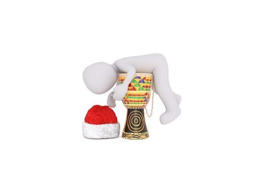 grafika przedstawia kukiełkę leżącą na djembe obok której leży czapka św. Mikołaja