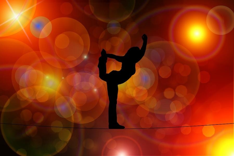 Zdjęcie przedstawia postać kobiety w pozycji gimnastycznej.