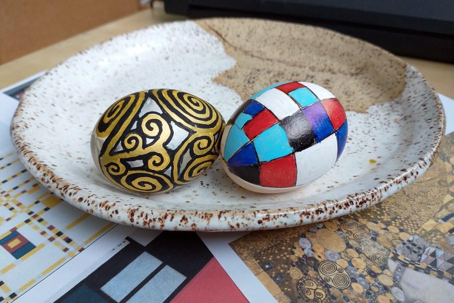 dwie kolorowe pisanki leżące na talerzu