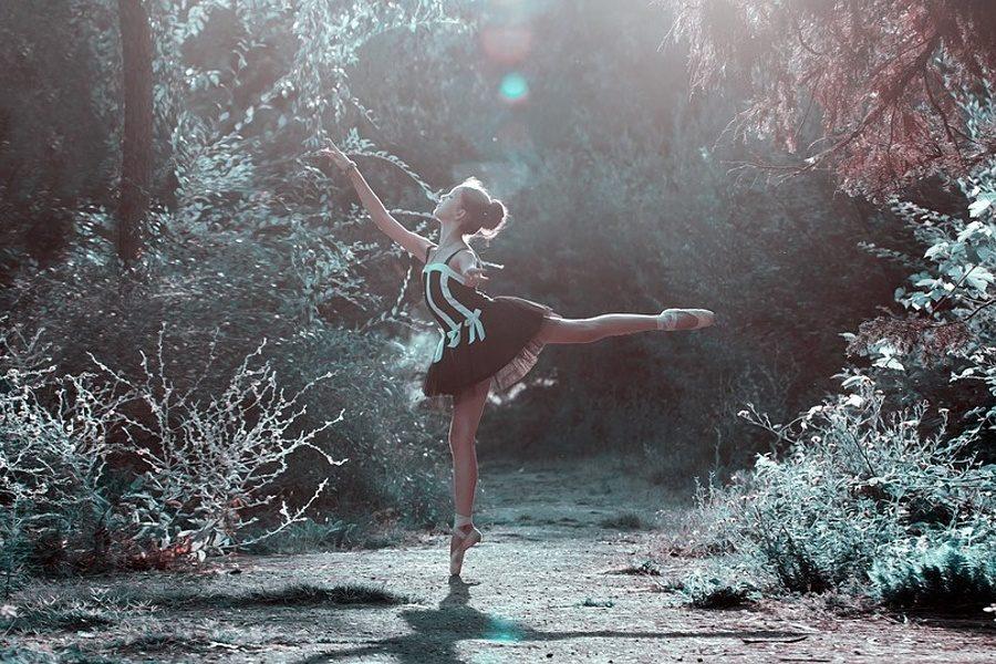 Zdjęcie przedstawia tancerkę stojącą wśród drzew i krzewów w pozie arabesque na pointach.