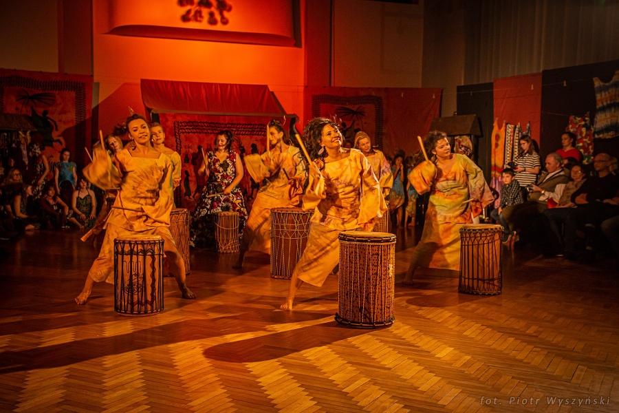 Kobiety ubrane w barwne suknie, trzymające drewniane pałki w rękach w tanecznej pozie. Przed każdą stoją bębny afrykańskie.