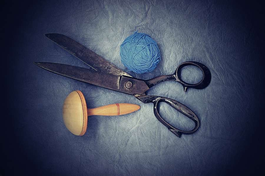 Zdjęcie przedstawia stare nożyczki, drewniany naparstek i niebieski kłębek nici.