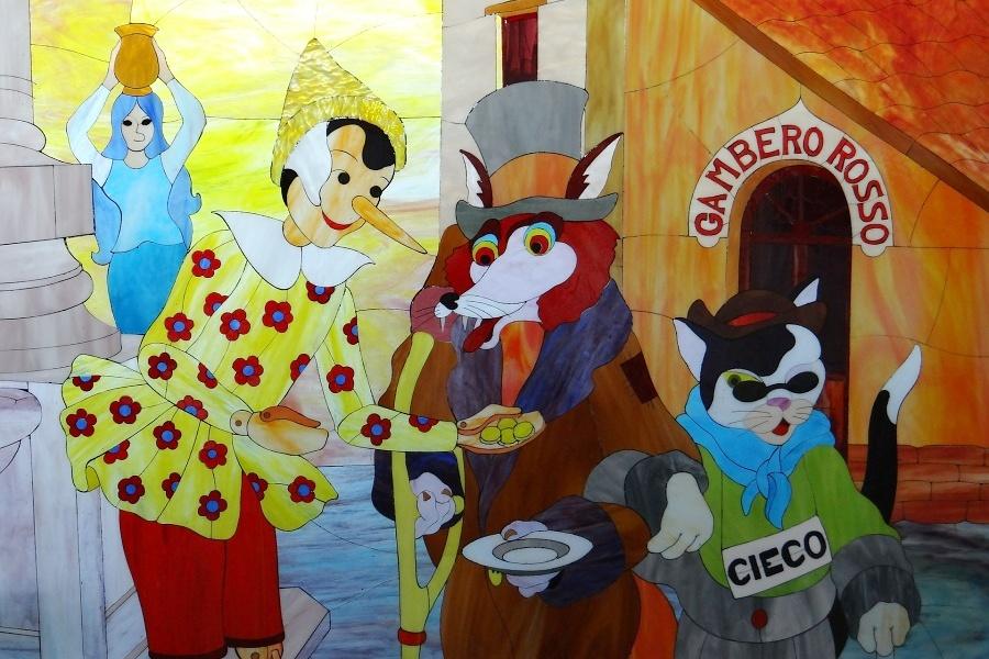 Zdjęcie przedstawia kolorowy rysunek, który przedstawia Pinokia, Lisa i Kota.