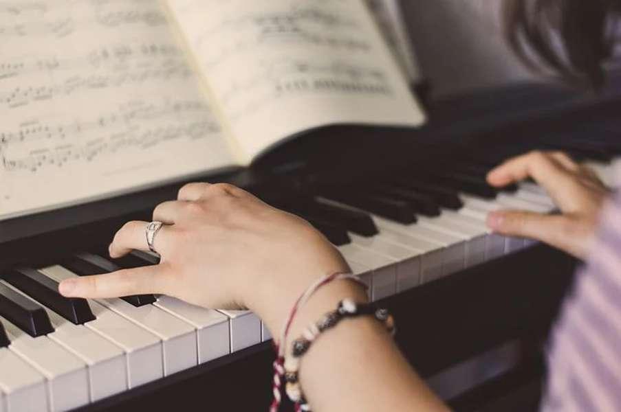 dłonie kobiety grającej na pianinie