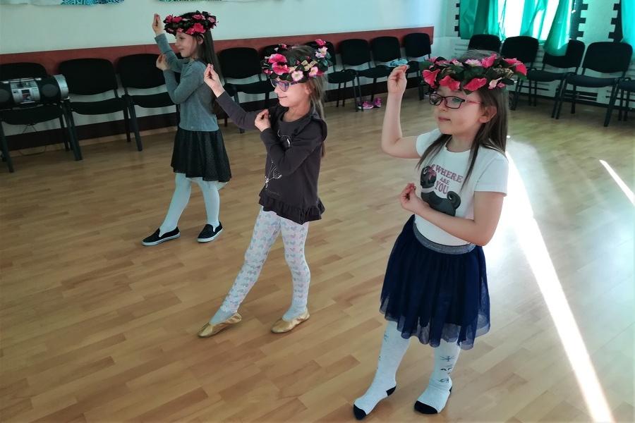 dziewczynki tańczące przed lustrem, na głowach mają wianki