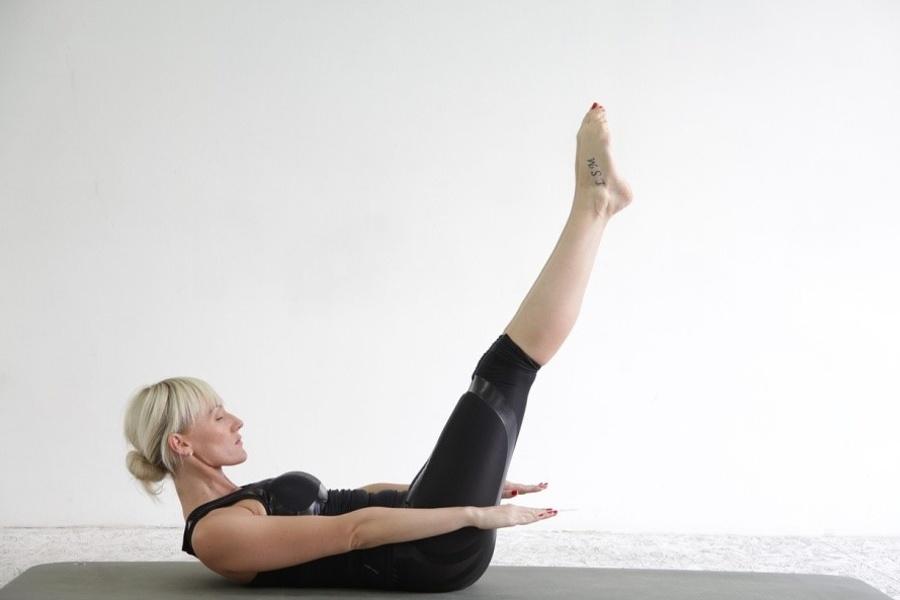 kobieta w leżeniu tyłem z uniesionymi nogami i głową