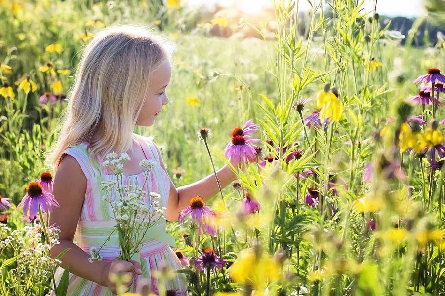 dziecko na łące pełnej kwiatów