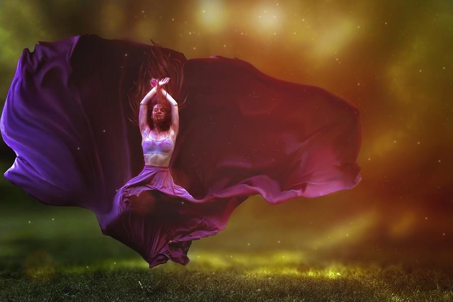 Zdjęcie przedstawia postać tancerki w zwiewnej długiej fioletowej spódnicy unoszącej się nad głową.