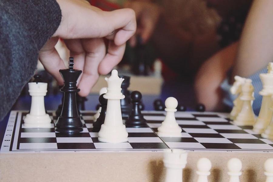 dłoń wykonująca posunięcie podczas gry w szachy