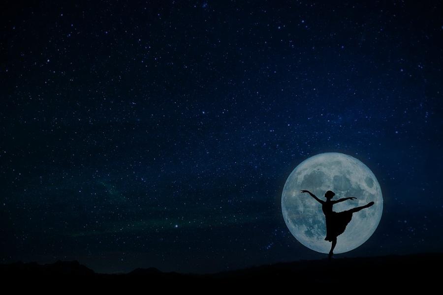 Zdjęcie przedstawia baletnicę na tle pełni księżyca w pozie arabesque