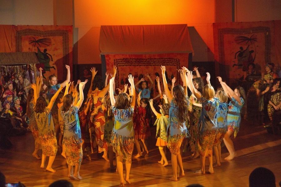 > Grupa dziewcząt na scenie w niebieskich i czerwonych tunikach, przodem do > koła z rękami uniesionymi do góry.