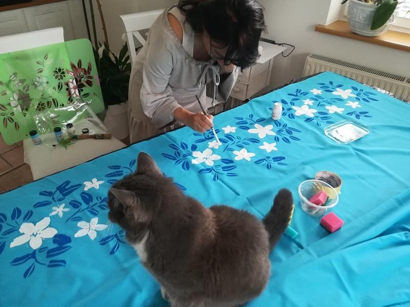 Kobieta malująca kwiaty na tkaninie z siedzącym obok kotem.