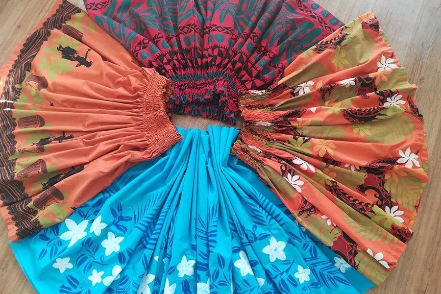 Cztery spódnice hawajskie leżące w kole.