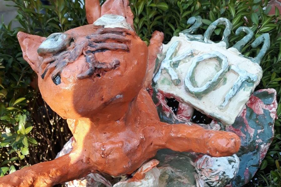 rzeźba kota na tle zieleni