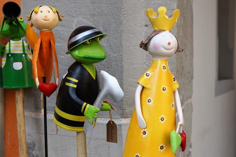 Zdjęcie przedstawia cztery teatralne lalki, na pierwszym planie żaba i królewna